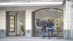 Passersby look in the windows of trendy shops on the streets of Milan Stock Footage