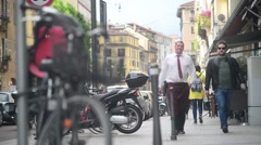 People pedestrians walking by street of center Milan Italy spring day Stock Footage