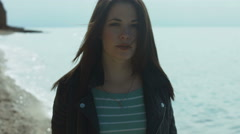 Attractive girl walking along a deserted seashore Stock Footage