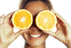 Young smiling afro american woman with half oranges, lifestyle concept isolated Stock Photos