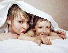 Young blond woman with little boy in bed, mother and son, happy familyyoung Stock Photos