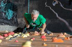 Mature Athlete Fixing Rope into Belaying Device - stock photo