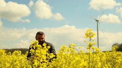 Happy man talking at the cell phone on the field of rapeseed - stock footage