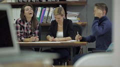 Three young people laughing and discussing something sitting at a desk in the Stock Footage