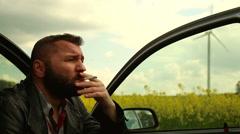 Sad man smoking, sitting in car Stock Footage