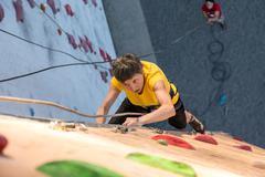 Aged Woman Climbing Wall - stock photo
