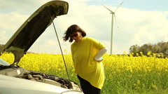 Woman with broken car in countryside Stock Footage