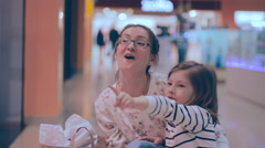 Mother and daughter shoping, walking at trade center, looking at storefront - stock footage