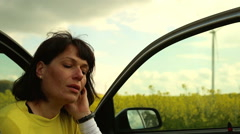 Pensive woman sits in car on the field of rapeseed - stock footage