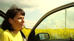 Smiling woman relaxes and tying hair, sitting in car Stock Footage