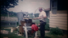 3285 homeowner uses a table saw to cut siding on house - vintage film home movie Stock Footage