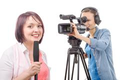 young woman journalist with a microphone and camerawoman - stock photo