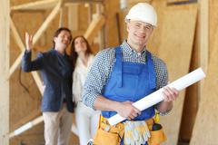Worker and house design plans - stock photo
