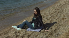 Thoughtful young woman sitting on bedding near the sea Stock Footage