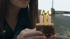 Girl blows out the candles on the cake Stock Footage