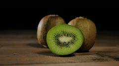 Sliced kiwi on wooden table dolly motion Stock Footage