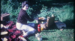 3290 mom cooks a picnic lunch on an outdoor grille - vintage film home movie Stock Footage