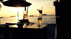 View of summer cocktail with umbrella during sunset on beach Stock Footage