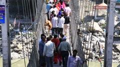 People crossing Laxman Jhula footbridge on river Ganges. Rishikesh, India Stock Footage