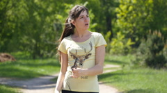 Girl running on forest path in a park and taking breath after jogging. - stock footage