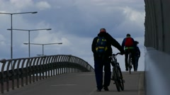 Tired Bicyclist carrying his bike and going up on a steep using the bike lane - stock footage