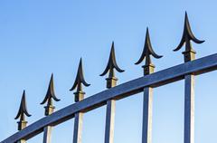 Spikes on Galvanised Gate Against Blue Sky Stock Photos