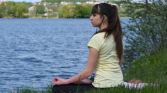 Young woman meditating and listening music on smartphone in lotus position. - stock footage