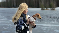 girl holds a dog Jack Russell standing on the dock of the lake - stock footage