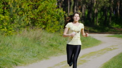 Girl running on forest path in a park and taking breath after jogging. Stock Footage