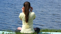 Young woman meditating and listening music in headphones in lotus position. - stock footage