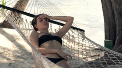 Sad, bored woman lying on hammock on beach Stock Footage
