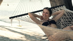 Woman waking up from sleep and stretching arms on hammock on beach Stock Footage