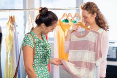 Woman selecting an apparel while shopping for clothes with her friend - stock photo