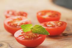 cut in half cherry tomatoes with basil leaf on wood table - stock photo