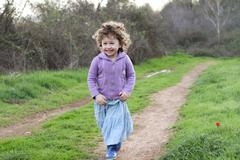 Cute little girl with boots runs in open field Stock Photos
