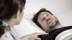 Doctor talking to anxious patient in hospital closeup desaturated Stock Footage