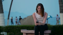 Woman typing with smartphone on the beach - stock footage