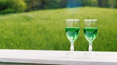 Two glasses with green carbonated beverage stand on a white table against the Stock Footage
