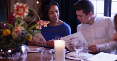4k, Happy attractive couple looking at a menu while sitting at a restaurant - stock footage