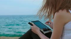 Woman surfing internet with tablet on the beach Stock Footage