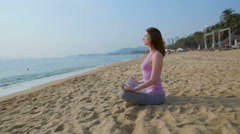 Woman meditate  on the beach close to blue sea ,slow motion - stock footage