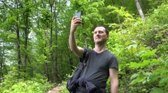 Happy man taking selfie photo with smartphone in a forest. Sound Stock Footage