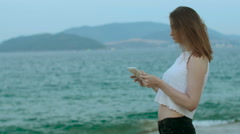 Girl doing selfie with tablet on the beach at sunset Stock Footage