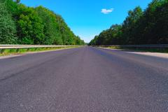 Empty highway and green forest - stock photo