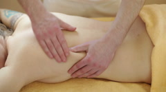 Massage. Manual therapist manipulates on woman's back side, close up - stock footage