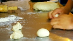 Closeup baker using both hands simultaneously rolling up small dough breads Stock Footage