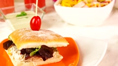 Delicious ciabatta sandwich sitting on elegant orange plate, slow upwards swipe - stock footage