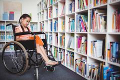 Girl in a wheelchair reading a book - stock photo