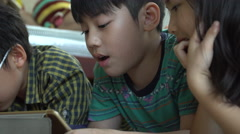 4K, Young asian child playing online games on tablet computer and smart phone . Stock Footage