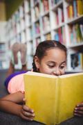 Close up of girl lying and reading a book - stock photo